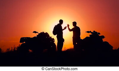 Silhouettes of men and ATVs at sunset. Men shake hands. -...