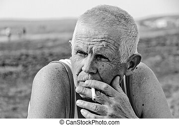 An elderly man smokes in nature He is thoughtful and lonely...