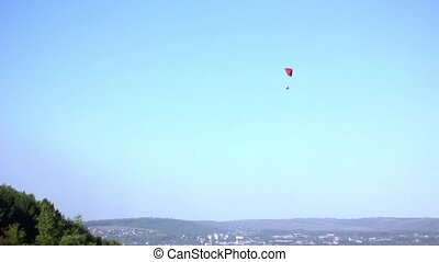 glider flying in the sky - One Paraglider Soaring In the Sky