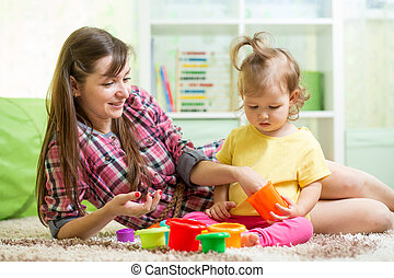 Kid toddler with babysitter playing on floor in the room -...