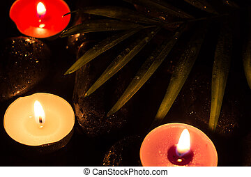 Scent colorful lighted candles on black wet stones and green...