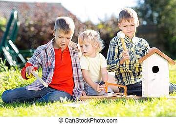 Kids brothers making nesting box together outdoors