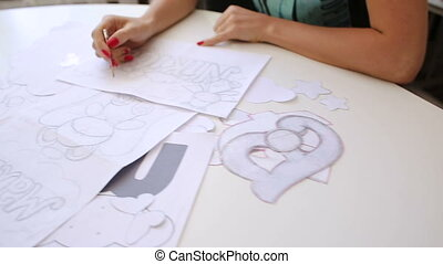 Female fashion designers drawing sketches for clothes in...