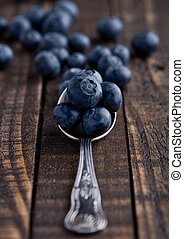 Blueberries on old spoon on grunge wooden board. Natural...