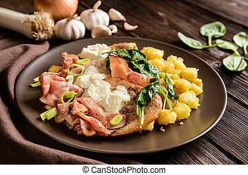Roasted pork cutlets with bacon, cheese, spinach and potatoes