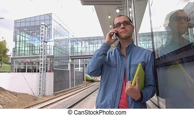 Man wearing black rim glasses talks on his mobile phone at...