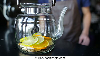 The bartender puts a lemon in a glass teapot
