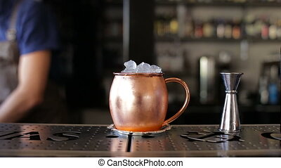Barman is decorated with a cocktail in a copper bowl