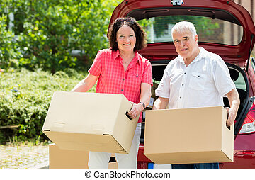 Senior Couple Standing In Front Of Car