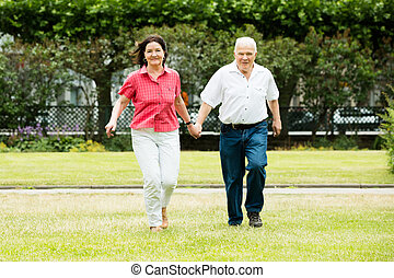 Couple Running In Park Holding Hands - Happy Senior Couple...