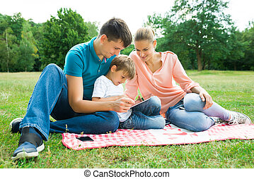 Family Using Digital Tablet In The Park