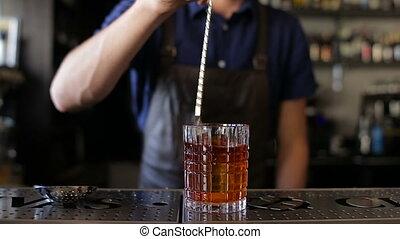 Bartender, barman preparing an alcoholic beverage, drink in nightclub, pub or bar