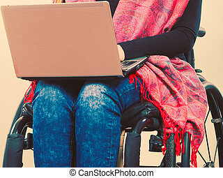 Crippled person with laptop. Young disabled female surfing...