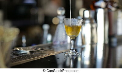 Bartender pouring strong alcoholic drink into small glasses...