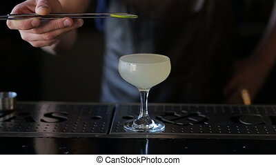 The hands of the bartender garnish the cocktail with lime -...