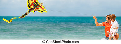 Beach fun - Panorama of happy dad and son flying a kite...