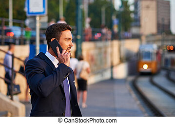 Young businessman in the tram stop - A handsome young...
