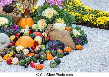 Freshly harvested summer vegetables among flower beds. Large...