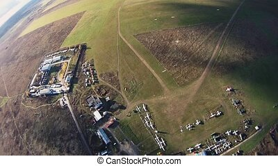 Skydivers parachuting in sky above green fields Extreme...