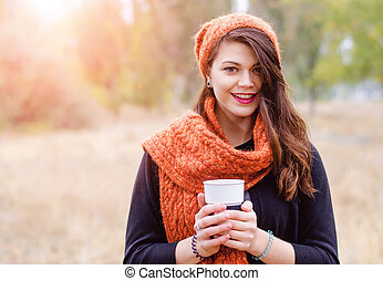 Young girl with a cup of coffee - Young smiling girl in a...