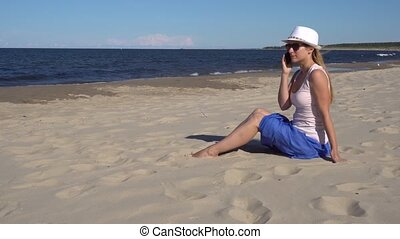 young woman talking by cell phone on the beach - young woman...