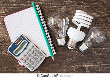 Lightbulbs and notebook with calculator - Three different...