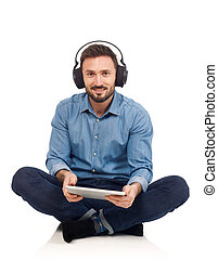 Leisure activity - Man with headphones and tablet looking at...