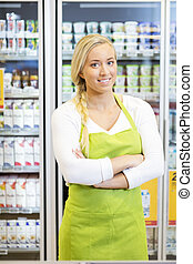 Female Worker Standing Arms Crossed In Grocery Store -...