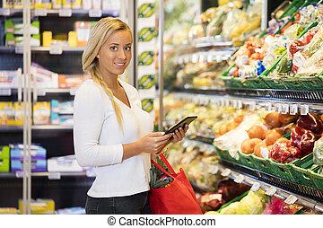 lebensmittelgeschäft, frau, Tablette,  digital, gebrauchend, Lächeln, kaufmannsladen