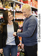 Happy Customers Using Smart Watch In Grocery Store - Happy...