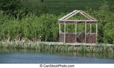 Wooden arbor on shore of pond