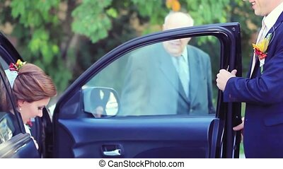 Groom open the door of wedding car and take hand to bride...