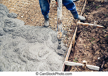 top close up view of worker handling a massive cement or...