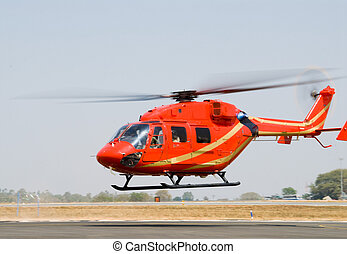 Helicopter - A red helicopter takes off
