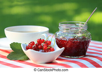 Red currant jam and tea - Jar of red currant jam and tea in...