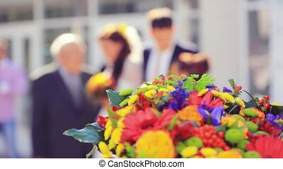 Wedding focused bouquet in the foreground and blurred of newlywed couple having fun in green sunny park. 1920x1080