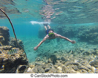 man is diving underwater with a mask with a tube for...