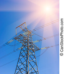 High-voltage power transmission towers in sunset sky background.