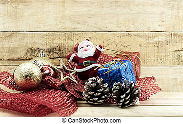 Little Santa Claus and small pine cone with snow ball and small gifts on wooden background.