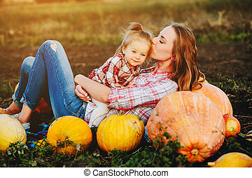 mother and daughter lie between pumpkins on the field,...