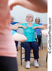 Group Of Seniors Using Resistance Bands In Fitness Class