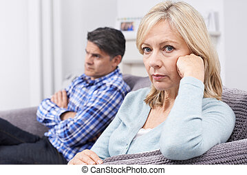 Mature Couple With Relationship Difficulties Sitting On Sofa