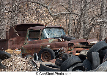 Junkyard - An old truck and tires in a junkyard.