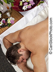 Man at a spa - A Caucasian man lies on a massage table with...