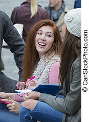 Headshot of red headed student - A happy young woman smiles...
