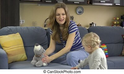 Babysitter woman have fun with baby girl on sofa at work....