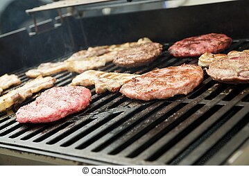 Barbecue with sausages, burgers and bacon - Preparation of a...
