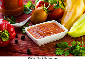 hot sauce adjika with fresh vegetables for cooking