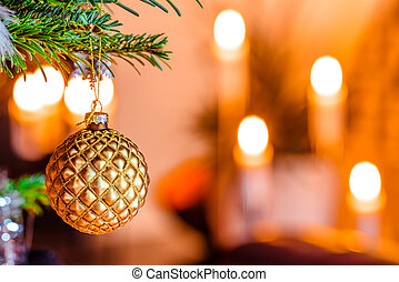 Golden bauble on a Christmas tree with candlelights in the...