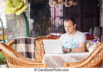 Man working on laptop at the wooden table outdoors -...